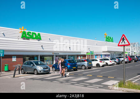 Two young ladies with small dogs useing zebra crossing at Asda store on Cherry Tree Retail Park Cherry Tree Road Blackpool Lancashire England UK - Stock Photo