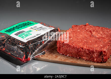 MORGANTOWN, WV - 8 October 2019: Packaging for Impossible Foods burger made from plants with raw product on steel background - Stock Photo