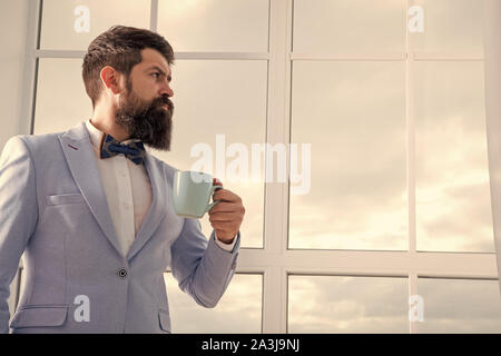modern businessman. thoughtful bearded man drink coffee. businessman in modern formal outfit. modern life. business man at window. future success. morning inspiration. copy space. modern office. - Stock Photo