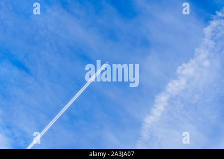 Airplane and trace, condensation trails, vapor trails. Bright blue sky background with diagonal jet plane trace - Stock Photo