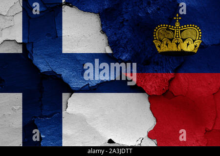flags of Finland and Liechtenstein painted on cracked wall - Stock Photo