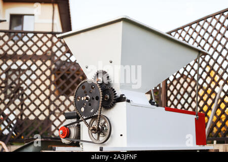 Automatic metal grape crusher for pressing grapes to make wine. Small business concept. Winemaking process. - Stock Photo