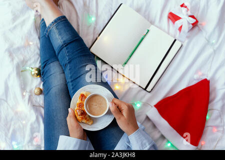 Young woman lying and having breakfast in bed. Christmas morning in a cozy bedroom decorated with Xmas lights and gifts. Happy young girl thinking on - Stock Photo
