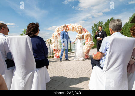 Novosibirsk, Russia - 06.15.2019: A wedding ceremony for the bride and groom in outdoor by the river with guests sitting on the chairs and a large dec - Stock Photo