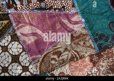 Batik material background, Indonesian material pieced together with white zigzag stiches in crazy quilt design in colorful blue green pink and brown c - Stock Photo