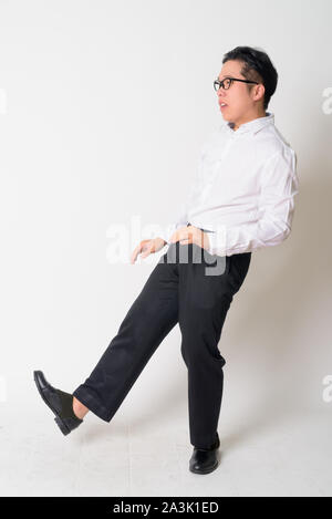 Portrait of stressed young Asian businessman with eyeglasses running away - Stock Photo