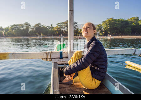 Young woman traveler meets dawn in the sea on a boat - Stock Photo