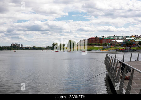 view from the embankment of the lower Kaban lake. colored catamarans in the form of cars float on water. lonely fisherman in the city on the waterfron - Stock Photo
