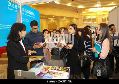 Tashkent, Uzbekistan. 8th Oct, 2019. Uzbek students communicate with a delegation of China's higher educational institution at an exhibition on higher education in China, in Tashkent, Uzbekistan, Oct. 8, 2019. An exhibition on higher education in China opened here Tuesday to familiarize Uzbeks with opportunities to study abroad in the East Asian country. Organizers said 30 leading higher educational institutions of China were presented at the event. Credit: Zafar Khalilov/Xinhua/Alamy Live News - Stock Photo