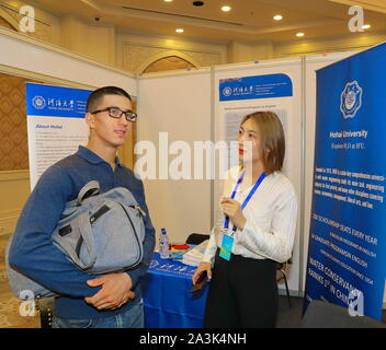 Tashkent, Uzbekistan. 8th Oct, 2019. A Uzbek student (L) communicates with an exhibitor at an exhibition on higher education in China, in Tashkent, Uzbekistan, Oct. 8, 2019. An exhibition on higher education in China opened here Tuesday to familiarize Uzbeks with opportunities to study abroad in the East Asian country. Organizers said 30 leading higher educational institutions of China were presented at the event. Credit: Zafar Khalilov/Xinhua/Alamy Live News - Stock Photo