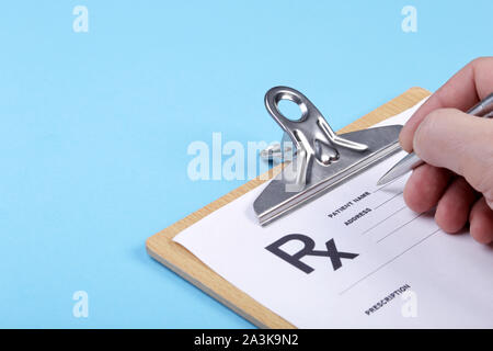 Male doctor filling patient complaints list clipped to pad. Physical, exam, disease prevention, ward round, prescribe remedy, healthy lifestyle - Stock Photo