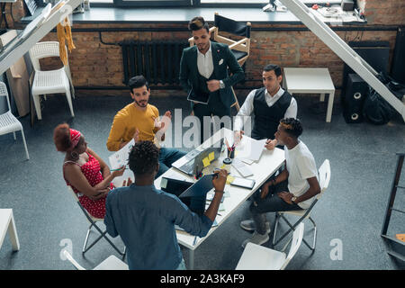 A team of young people work in the office. Meeting of businessmen in the office