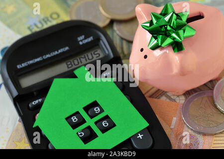 Piggy bank with calculator and paper house on euro money background - Concept of saving money to buy a home and money bonus - Stock Photo
