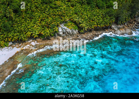 Aerial view of wild secluded lonely beach with rough granite rocks, white sand, palm trees in a jungle and turquoise water of the indian ocean at - Stock Photo