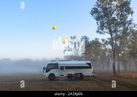 A Toyota Coaster motorhome camped at sunrise in the bush with yellow hot air balloons flying overhead, Mareeba, Queensland, QLD, Australia - Stock Photo