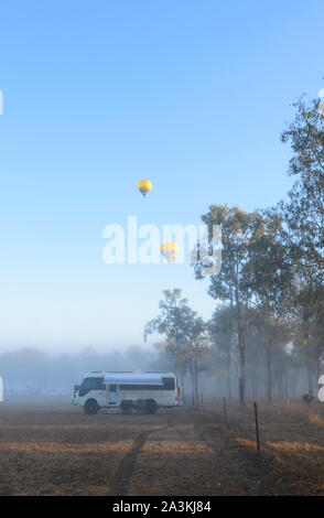 Vertical view of a Toyota Coaster motorhome camped at sunrise in the bush, with yellow hot air balloons flying overhead, Mareeba, Queensland, QLD, Aus - Stock Photo