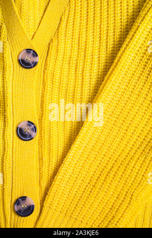 Yellow orange mustard ochre knitting wool texture background.Winter or autumn sweater or jumper with buttons close-up.Vertical orientation,flat lay - Stock Photo