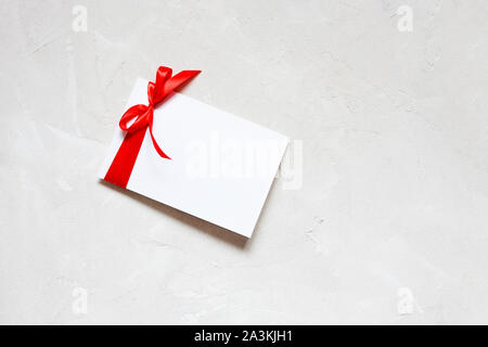 White paper note greeting card template with red ribbon bow on white textured background.Flat lay,top view,copy space - Stock Photo