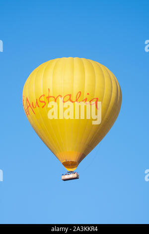 Yellow hot air balloon in flight with Australia written on it, Mareeba, Far North Queensland, FNQ, QLD, Australia - Stock Photo