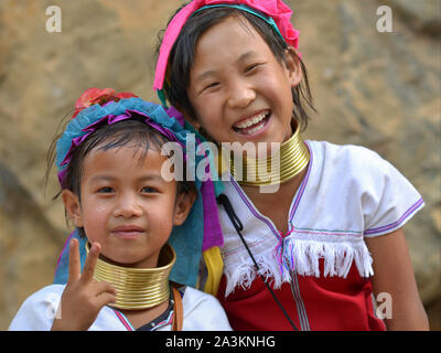Two Myanmarese Kayan Lahwi girls with tribal brass neck rings/coils pose for the camera.