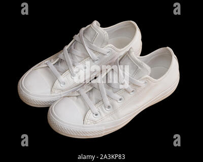 White trendy female leather sneakers closeup isolated on the black background. Woman style casual footwear - Stock Photo