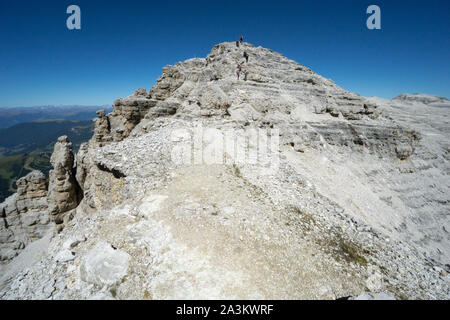 Dolomites mountain landscape near Passo Sella with many climbers heading to the summit and a stone cairn in the foreground - Stock Photo