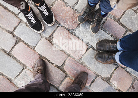 Feet of a family standing together on a paved street, top view