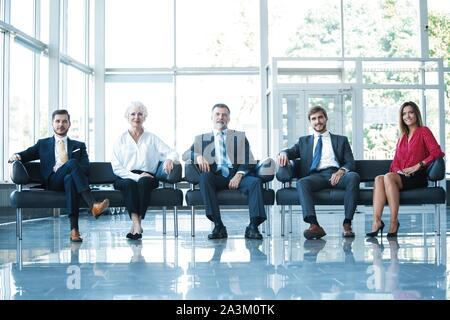 Confident business team sitting on chairs in a row.
