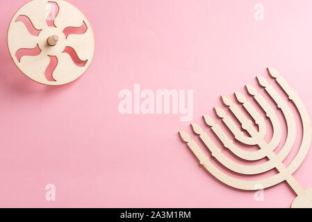 Children's craft Wood menorah candelabrum and wooden dreidels spinning top symbols Jewish holiday Hanukkah on pink background.Top view.Copy space for your text. - Stock Photo