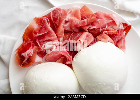 Two big mozzarella balls and prosciutto crudo or jamon on a white plate. Close up shot of delicious italian food - Stock Photo