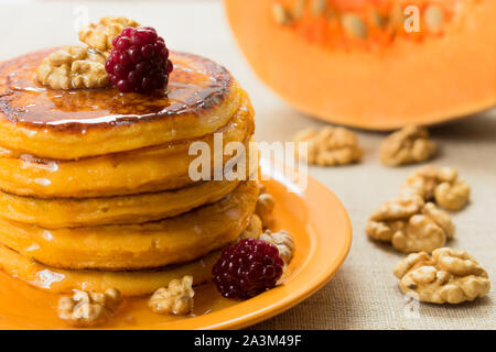 Pumpkin pancakes with honey and nuts, berries. End of seasonal (autumn) breakfast. - Stock Photo
