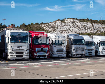 Heavy goods lorries parked at port of Dover transport terminal waiting for the ferry crossing between Dover and the French port of Caiais - Stock Photo