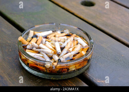 Ashtray full of cigarette butts on a table after the rain - Stock Photo