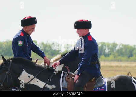 Samara, Russia - August 17, 2019: Young Cossacks in traditional costumes on horseback - Stock Photo
