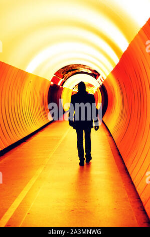 silhouette of a young man in black walking down a modern tunnel in stockholm - Stock Photo