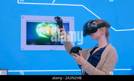 Young woman using virtual reality headset and drawing with special joystick - Stock Photo