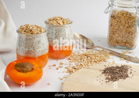Chia seed puddings with fresh apricot and oat meals on white with a space for text. Clean eating, dieting food concept - Stock Photo