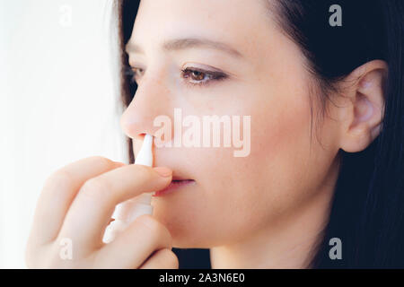 Nasal Spray. Closeup Of Beautiful Young Woman's Face With Nasal Drops. Close-up Of Female Spraying Medical Nasal Spray In Her Nose. Cold And Flu, Heal - Stock Photo