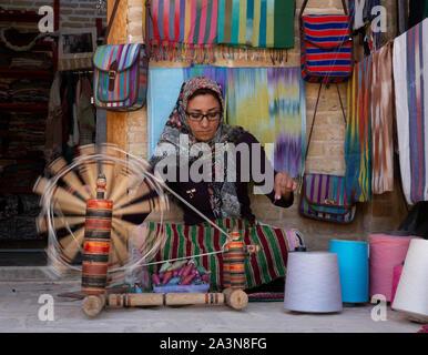 Isfahan, Iran - 2019-04-12 - Woman spins yarn on a manual spinner. - Stock Photo