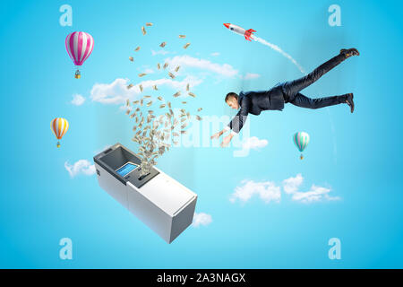 Businessman reaching to ATM machine with dollars flying out, hot air balloons and silver red space rocket in the air on blue background - Stock Photo