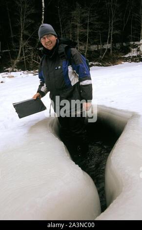 Man standing in ice-bound river Brasla in Gauja National Park Latvia - Stock Photo