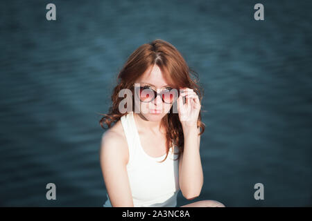 Redhead girl in sunglasses. close-up. emotions. Young redhead girl relaxing in sunglasses. woman relaxing outdoors. sinking eyes from the rays of the - Stock Photo
