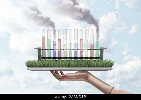 Test tubes filled with differently colored liquids, two tubes spouting smoke, standing on grass-covered screen of digital tablet held in woman's hand. - Stock Photo