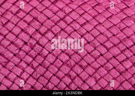 textile background - weaving of summer straw hat from toyo fibers colored in pink color close up - Stock Photo