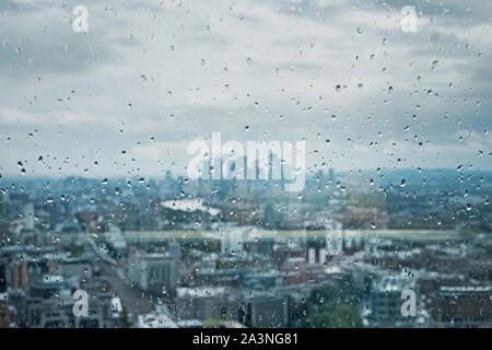 Drops of rain on the glass on the background of London city. Focus on drops. - Stock Photo