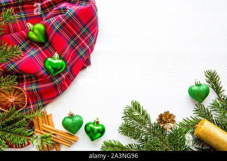 Christmas background with empty space for text. Green heart shape balls, golden candles, fir tree branches decorations on white table background. Red - Stock Photo