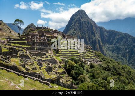 Machu Picchu city from the inside. Huayna Picchu mountain and green vegetation can be seen. Cloudy day. Archaeological site, UNESCO World Heritage, Pe - Stock Photo