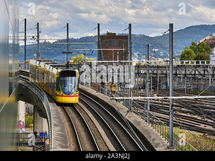 Tram Moving On Railroad Track In City Against Cloudy Sky - Stock Photo