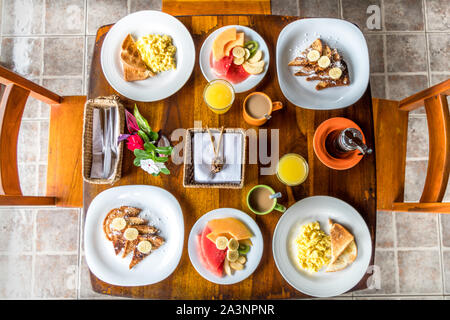 Full American Breakfast with coffee, orange juice, fresh fruits, eggs and french toasts for two - Stock Photo