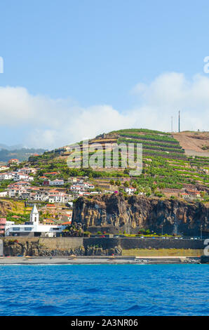 Beautiful small fisherman village Camara de Lobos in Madeira Island, Portugal photographed from the waters of the Atlantic ocean. Picturesque city on a hill by the coast. Tourist destination. - Stock Photo